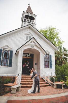 bride and groom kissing in front of chapel